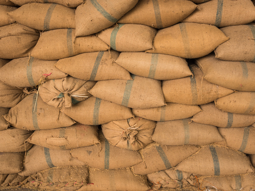 Old hemp sacks containing rice placed stacked in a row