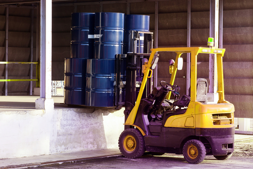 forklift carrying load of shipping drums to loading dock