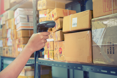 worker scanning package barcode on racking system