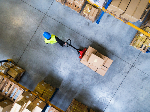 Male warehouse worker pulling a pallet truck