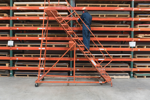 man on ladder with stacking racks and stored pallets