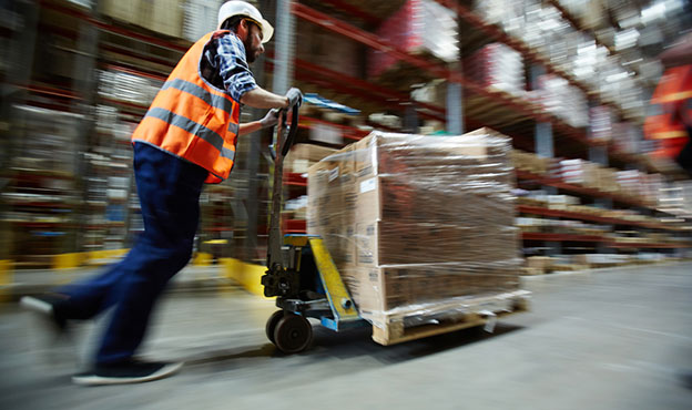 man pushing package in warehouse