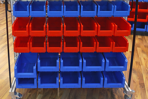 Red and blue plastic bins at sorting shelf in warehouse