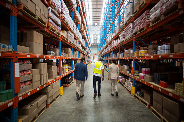 Rear view of warehouse team discussing while walking in warehouse