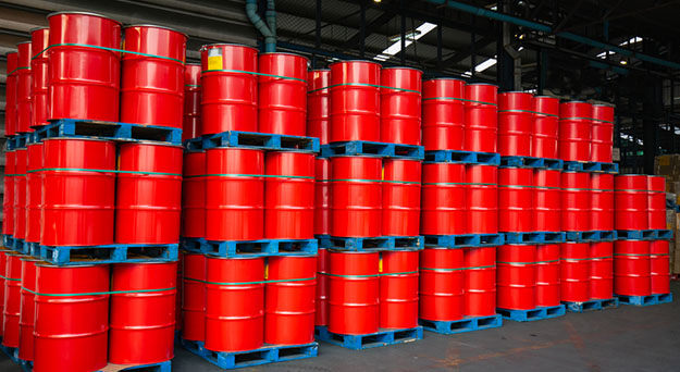 red steel drums stacked in warehouse