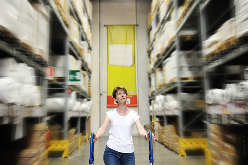woman pushing cart through factory aisle
