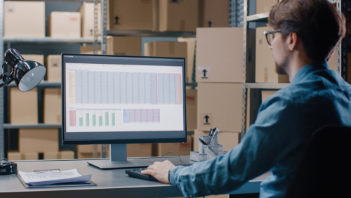 warehouse manager checking shipping spreadsheet