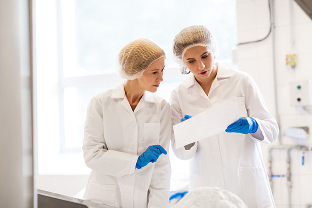 two laboratory technicians review paperwork