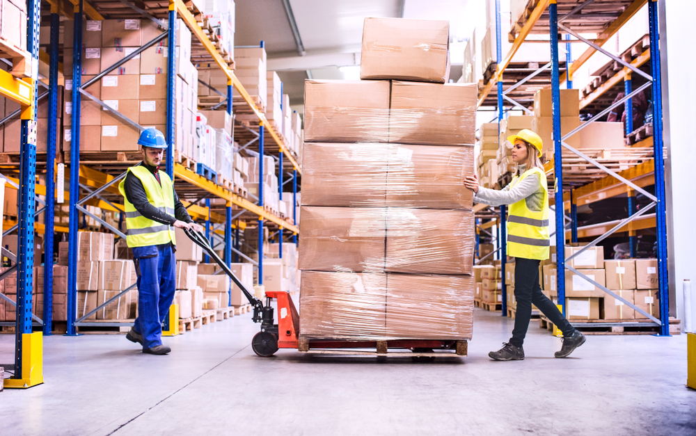 a pair of warehouse workers pulling a pallet jack