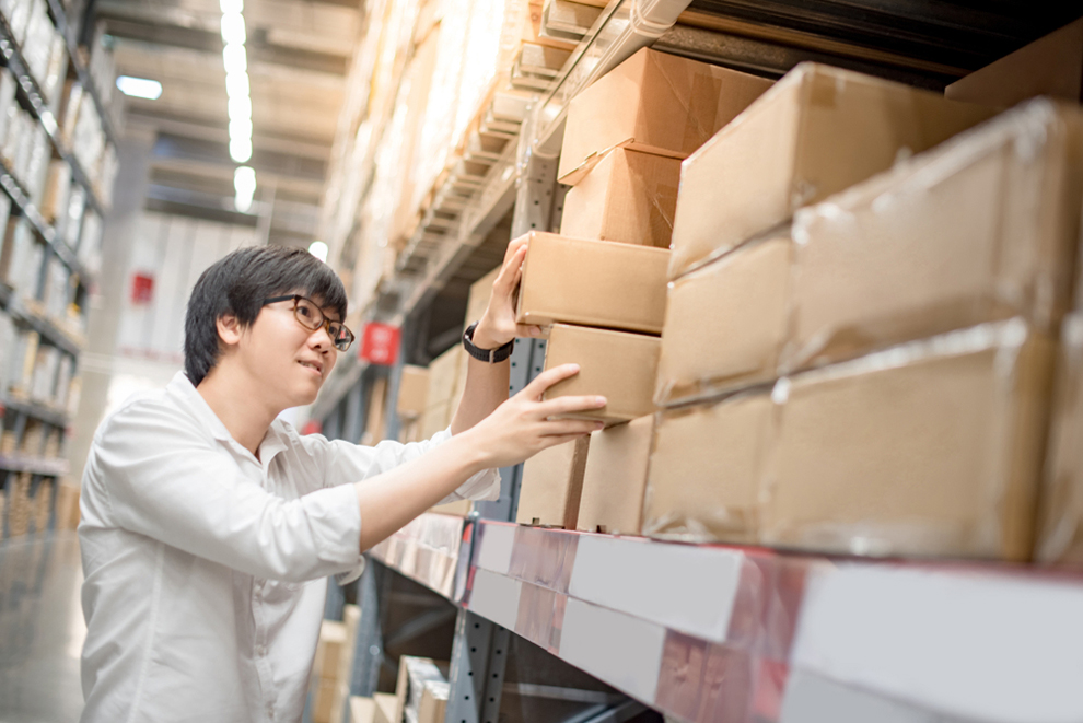 a worker picking a box from a shelf