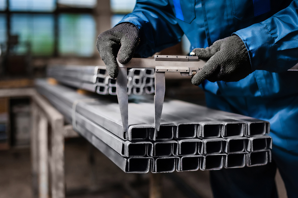 a factory worker measuring the profile of a metal bar