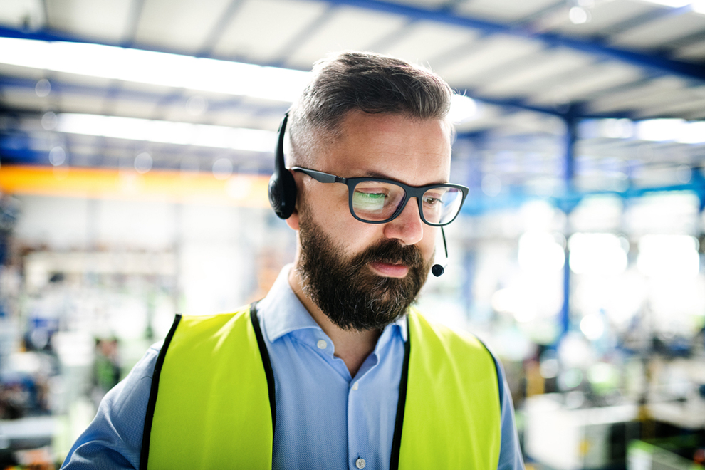 a technician with a high vis vest and a headset