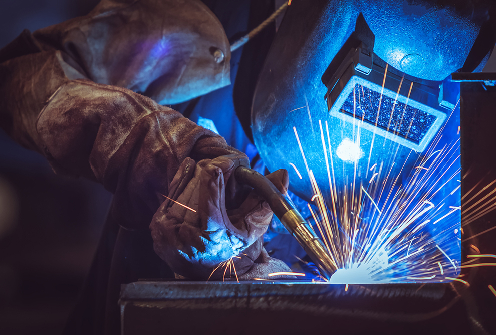 a worker welding with a welding mask on