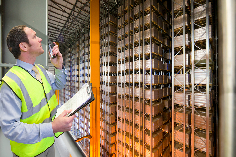 a worker with a walkie talkie and a clipboard surveying a warehouse