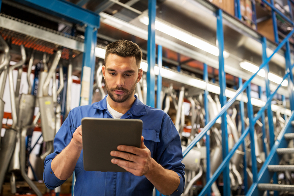 a worker using a tablet in an automotive warehouse