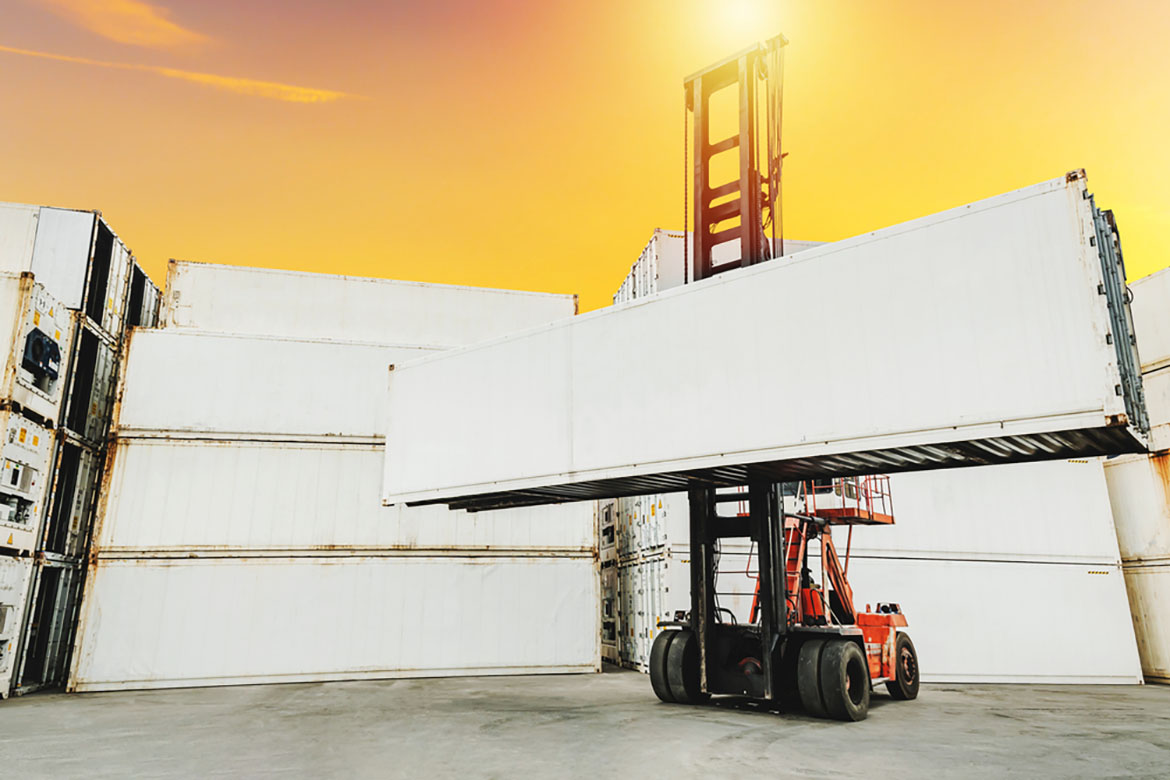a white shipping container being lifted by a forklift in  a shipping yard