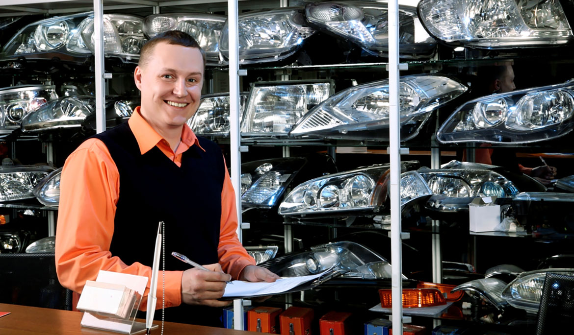 a smiling salesman in an autoparts store in front of assorted headlights