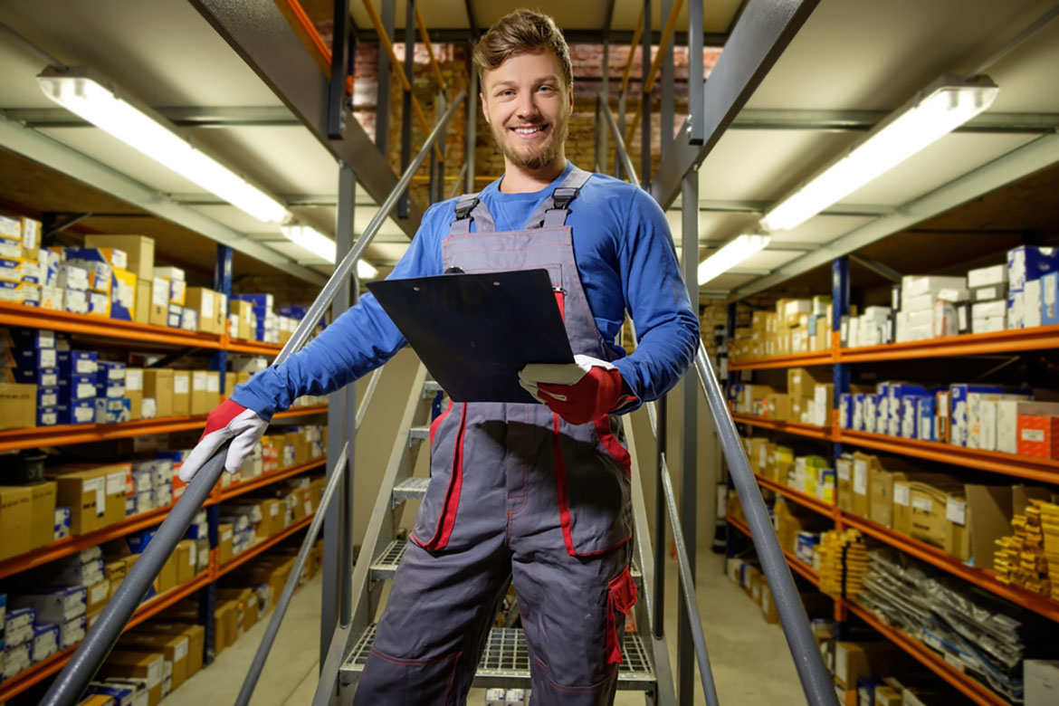 a worker standing on a staircase in an automotive warehouse